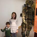 kids standing next to soldier manekin