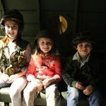 3 kids wearing army uniform and helets inside model aircraft