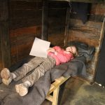 lois laying on a wooden bed in the trench