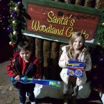 kids holding their gifts from Santa next to the Santa's Grotto sign