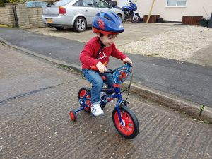 Cody riding spiderman bike with stabilisers