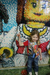 lois standing in front of the legoland hotel wall mosaic