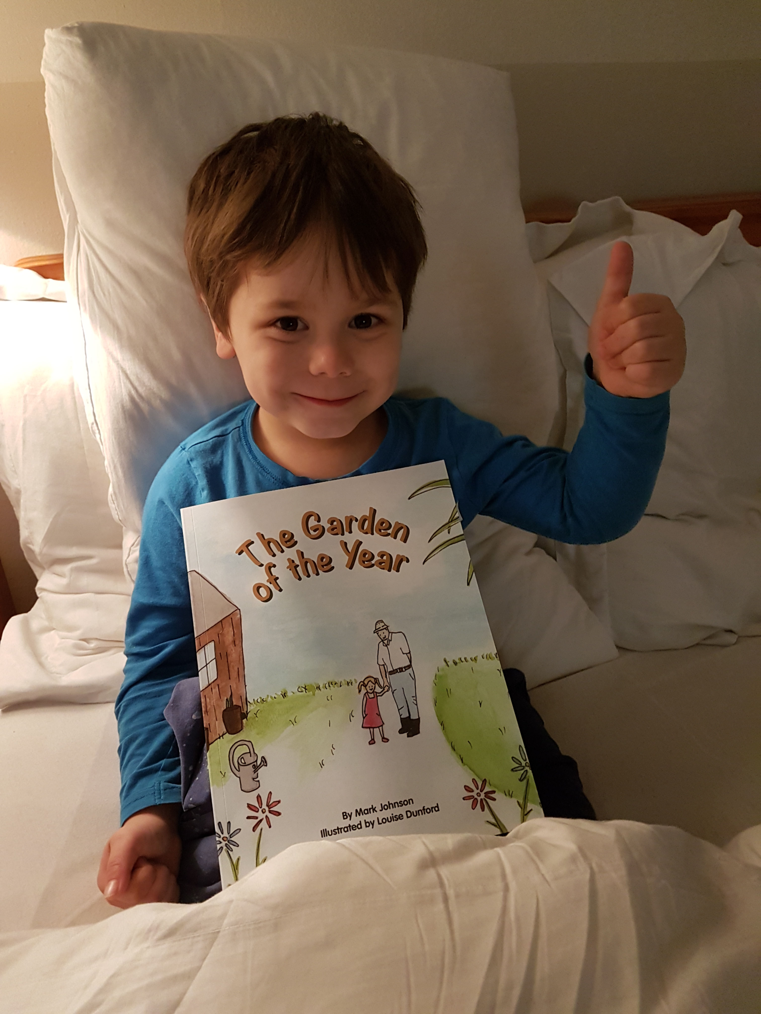 cody thumbs up holding book