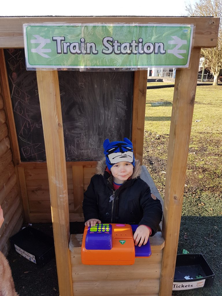 cody playing in the wooden pretend ticket booth