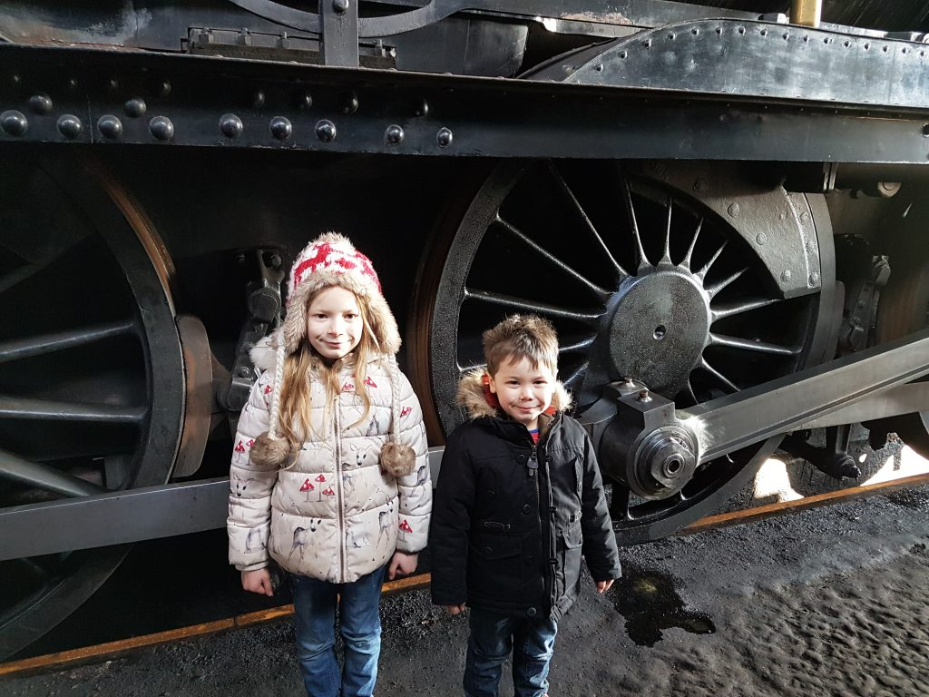 lois and cody stood beside wheels of steam train