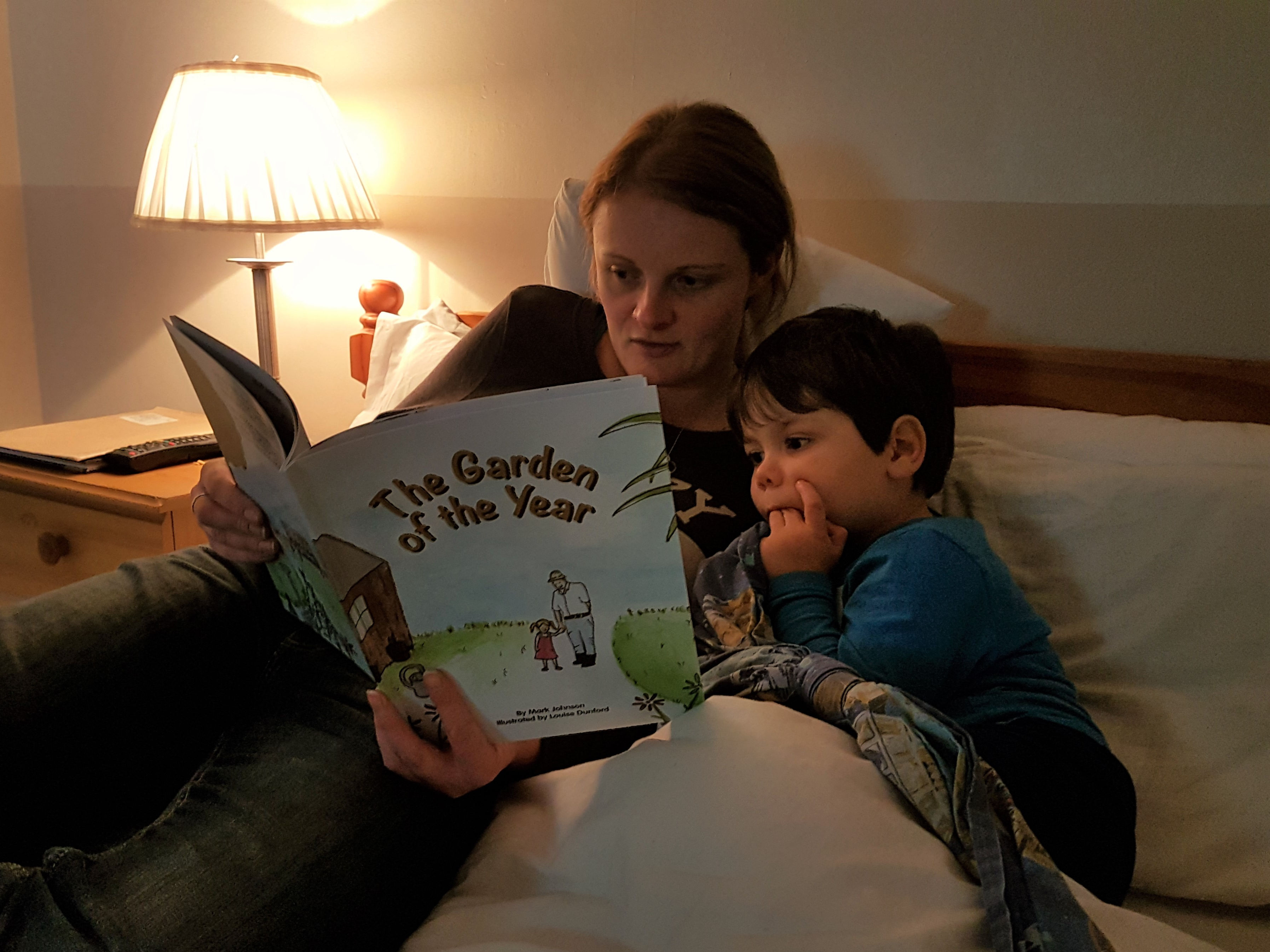mummy and cody sat in bed reading a book