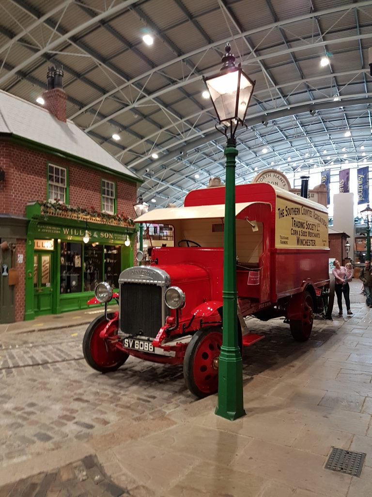 Red delivery truck parked on cobbled street in Milestones Living Museum
