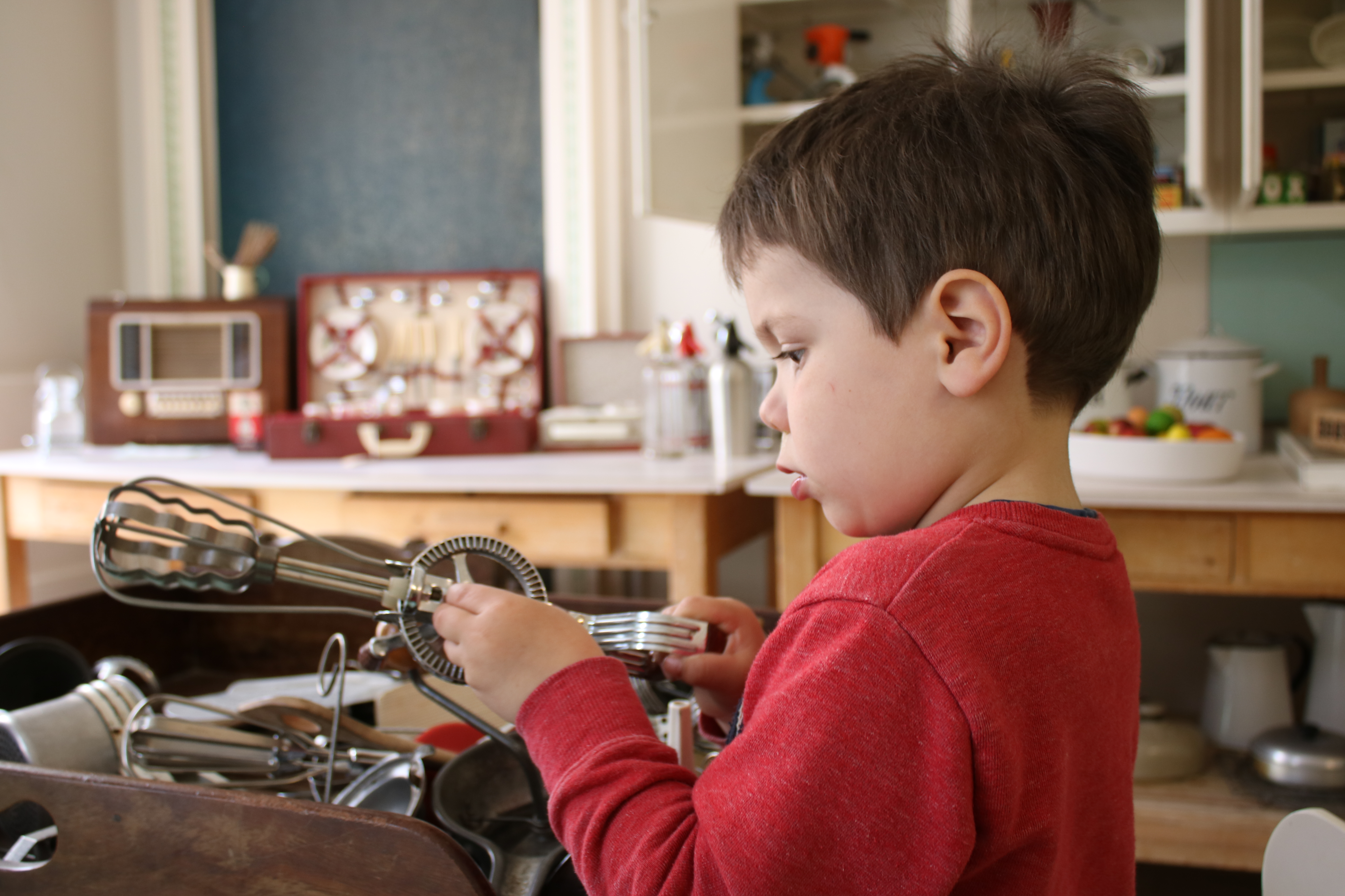 cody playing with kitchen utensils in the old kitchen