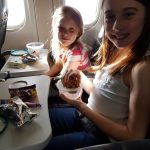 Lois and Lilian eating their snack pots on the plane