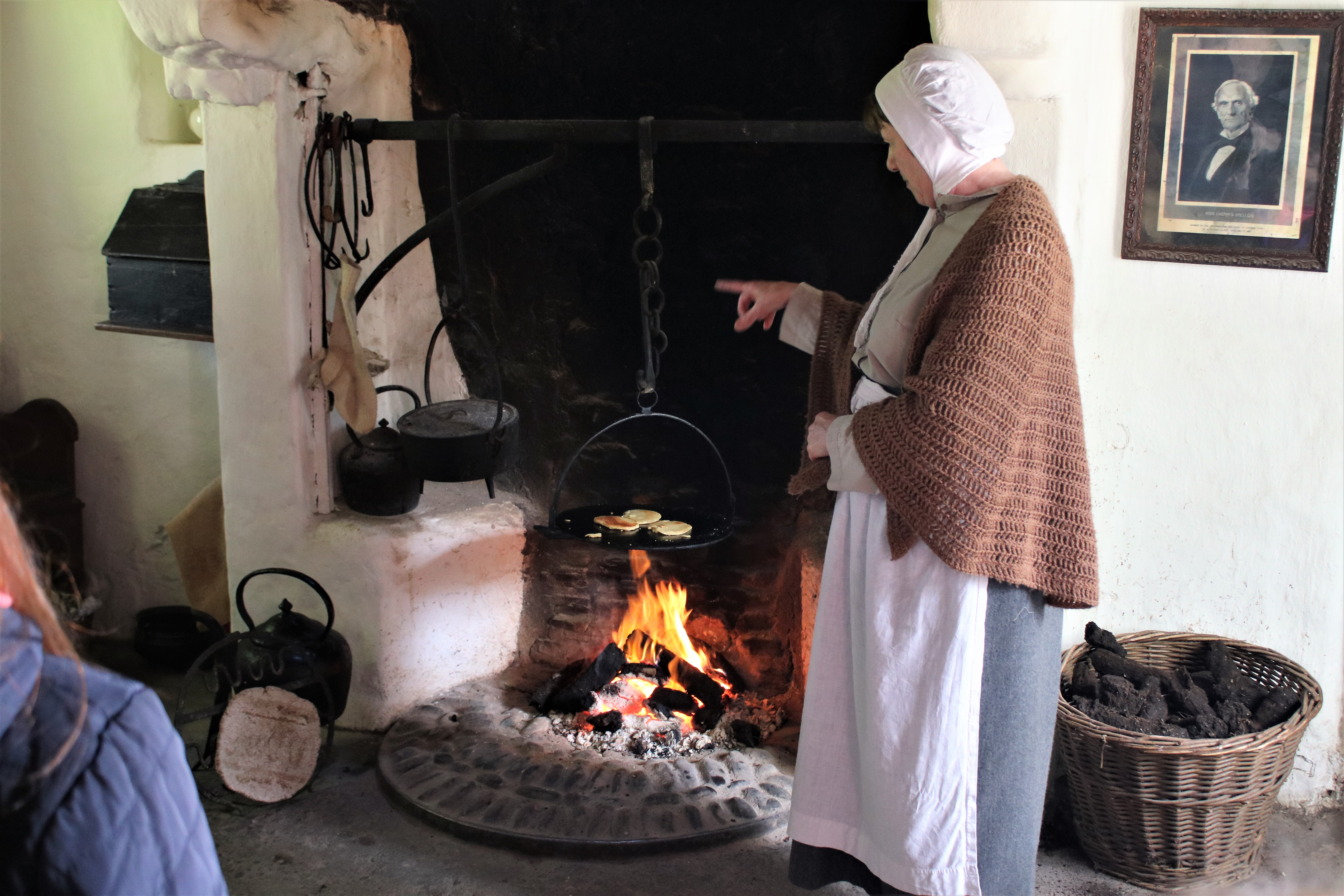 living history lady stood cooking on open fire