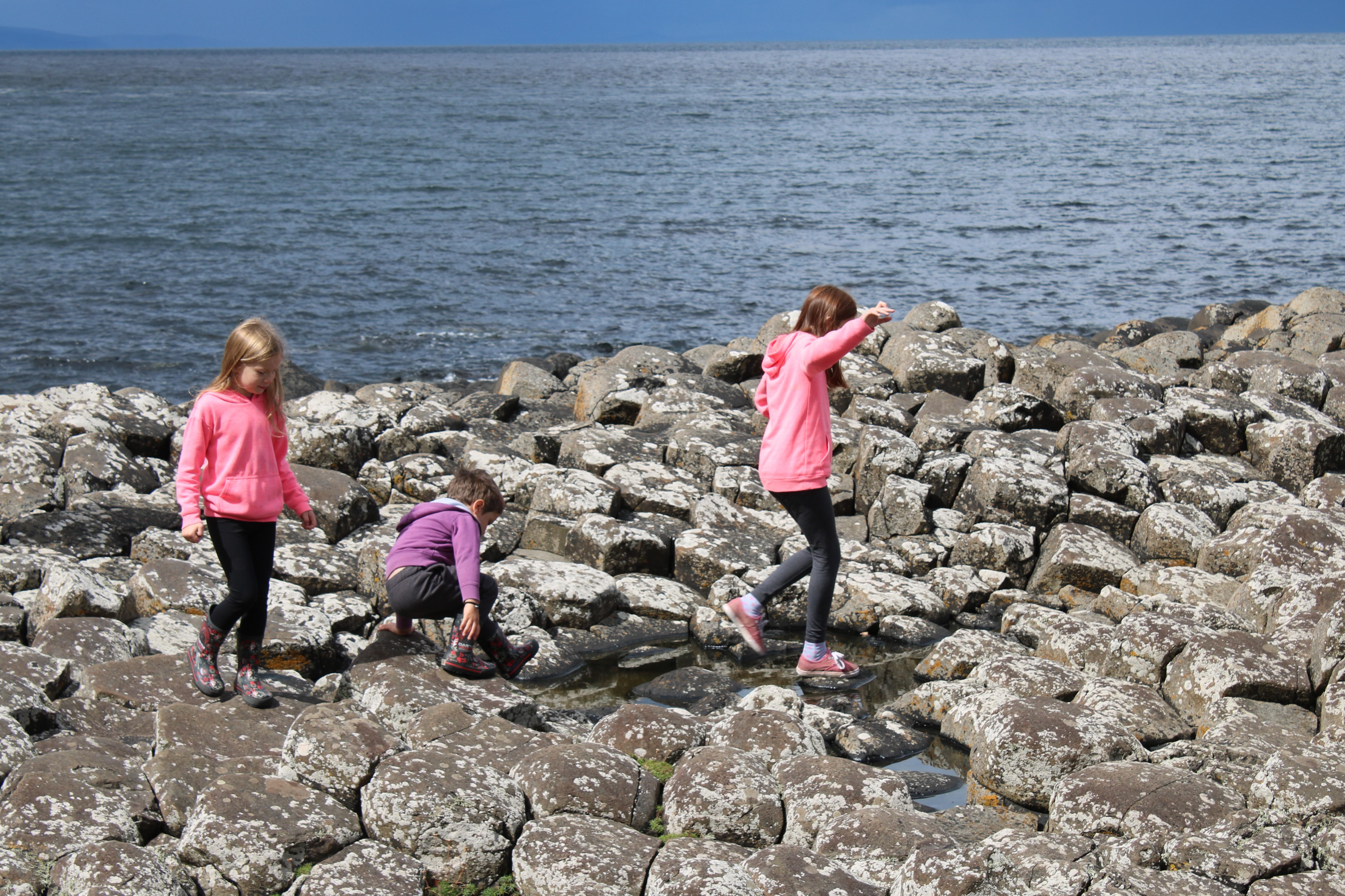 kids climbing across the rocks at The giants Causeway