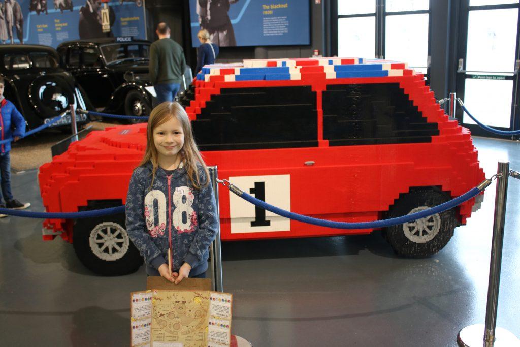 Lois stood beside lego car