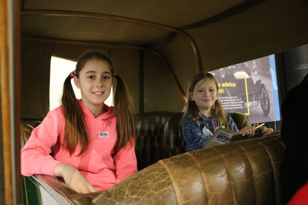 girls sat in back of old car