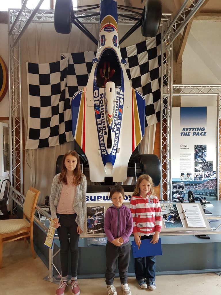 kids stood in front of Williams F1 car hanging on the wall