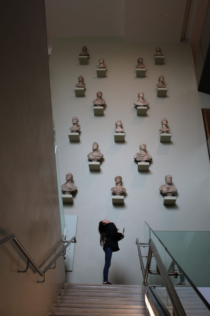 lilian stood beneath huge staircase wall of stone busts