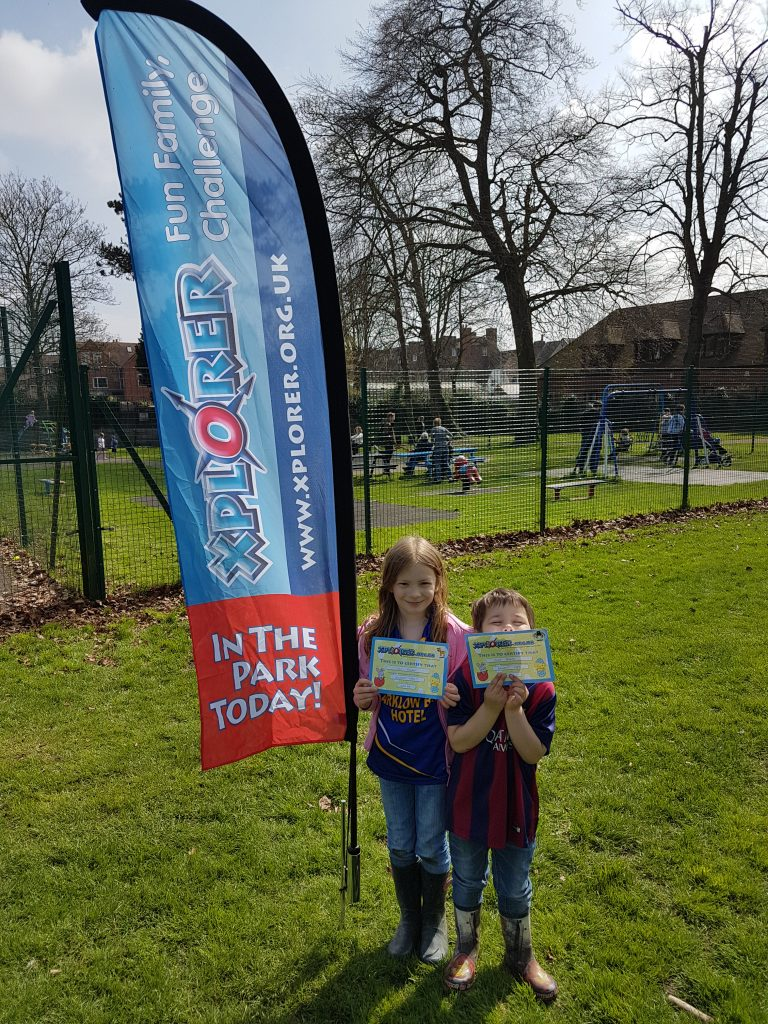 kids holding their Xplorer certificates next to Xplorer banner in the park