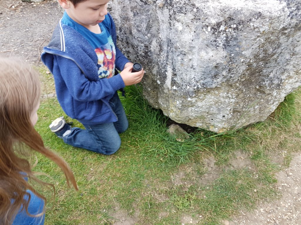 Cody finding a geocache under a large rock