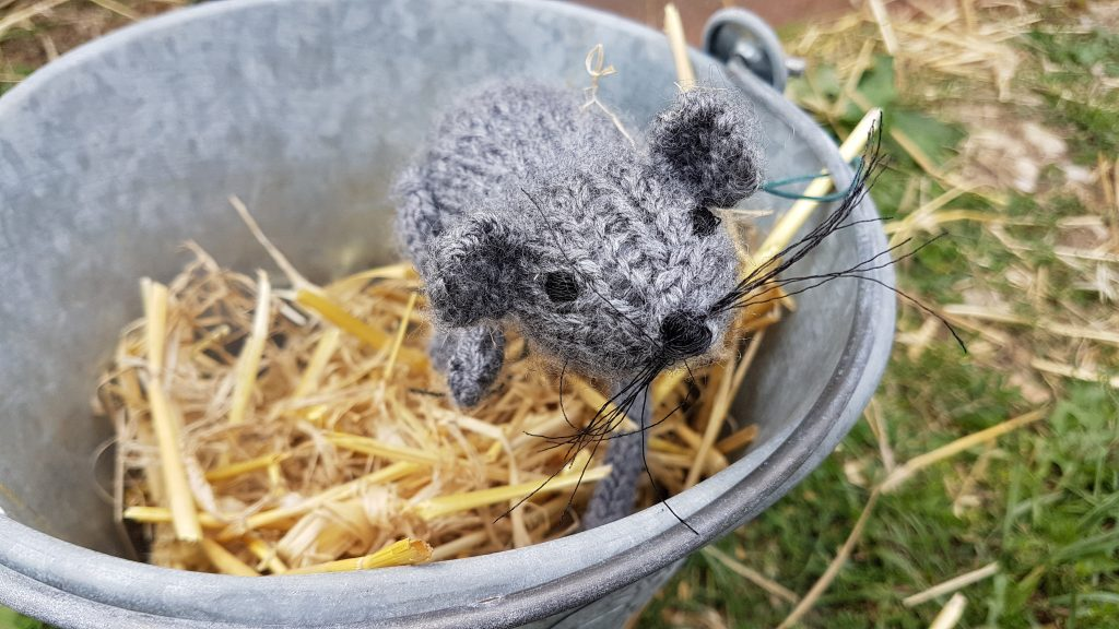 crocheted mouse in a bucket with hay