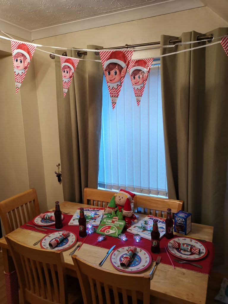 Breakfast table set up with elves, elf bunting, crackers and fairy lights