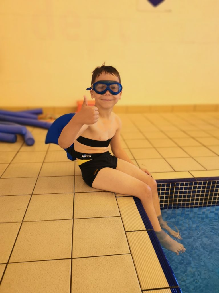 Cody sat on the edge of the pool giving thumbs up wearing his goggles and Swimfin