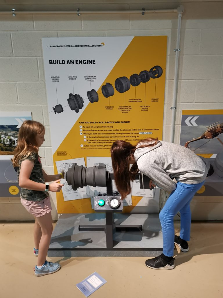 Lois and lily building an engine using the instructions on the wall