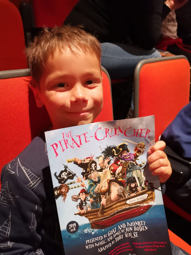 Boy sat in audience holding The Pirate Cruncher show leaflet
