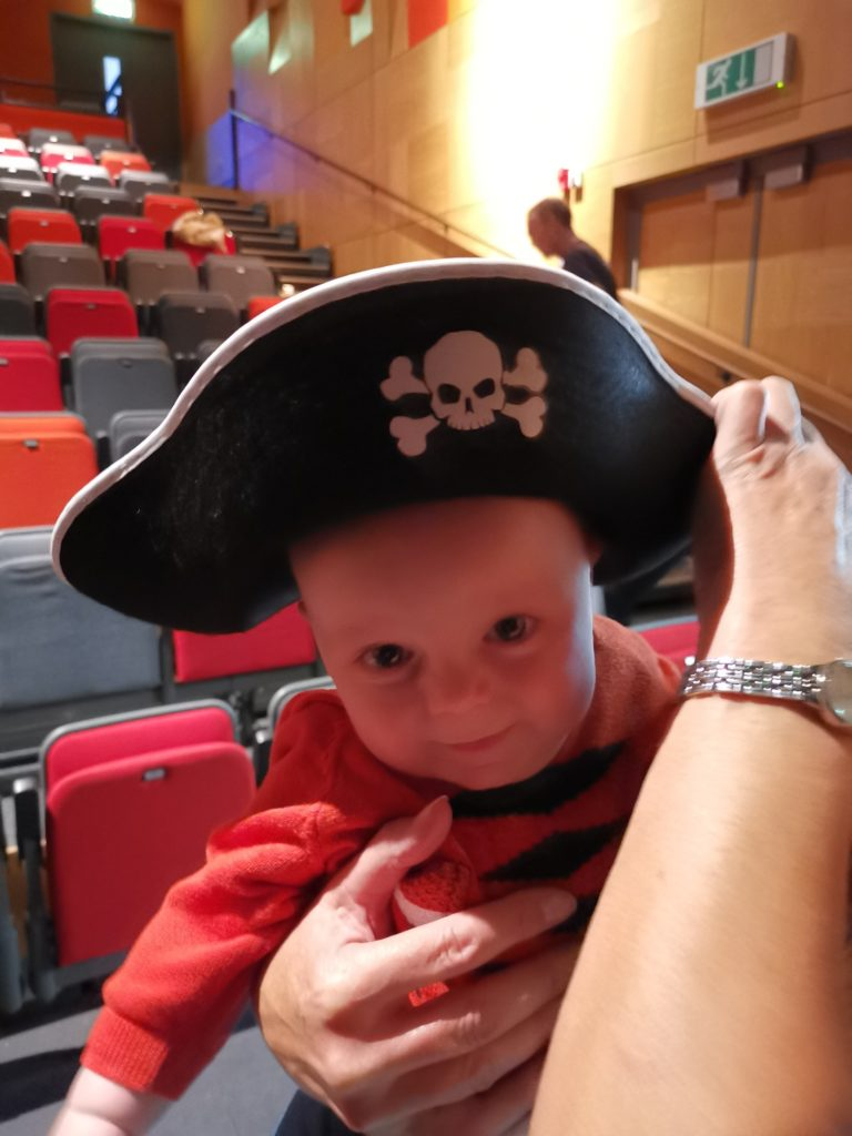 Baby wearing a pirate hat in the auditorium at The Pirate Cruncher stage show