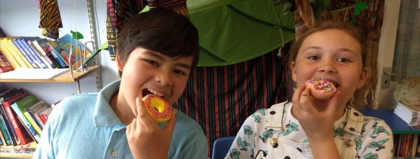 Boy and girl eating doughnuts at house of fun