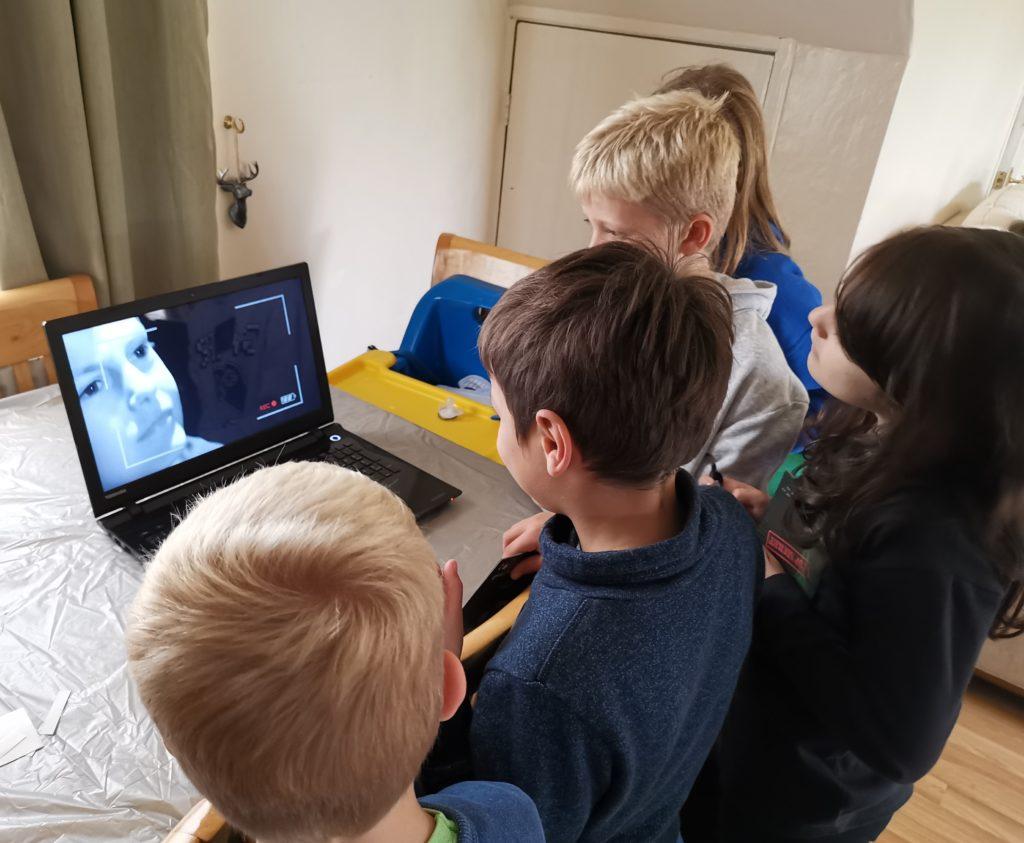 children gathered round laptop watching Spy:Co mission video