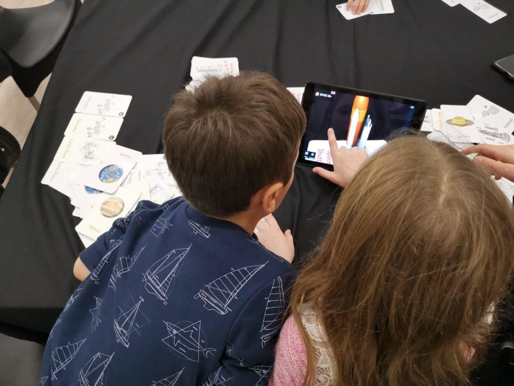 kids using the interactive cards and app on the ipads at the space store
