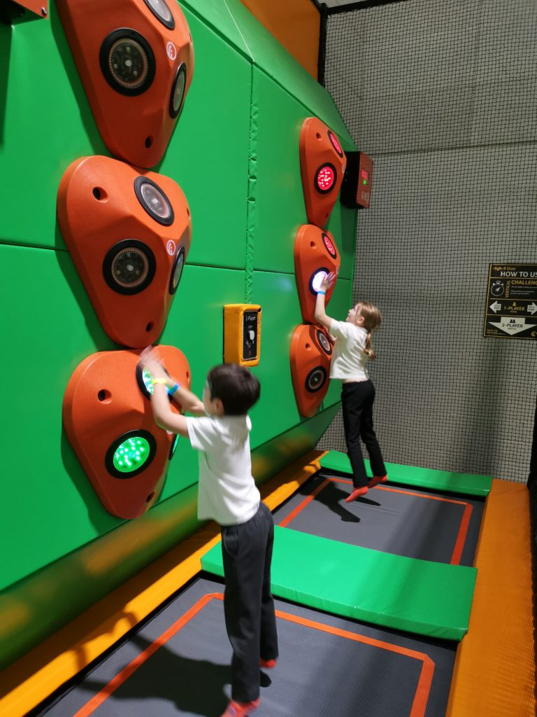 kids jumping to hit lights o the interactive boards above the trampolines