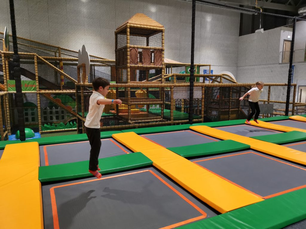 kids bouncing on the trampolines at carterton trampoline park with soft play area in the background