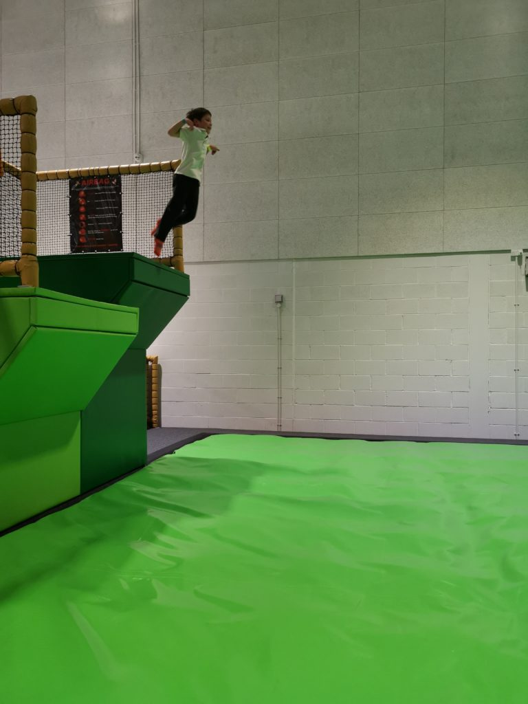 child jumping from the dive tower on to giant air bag in the trampoline park at carterton
