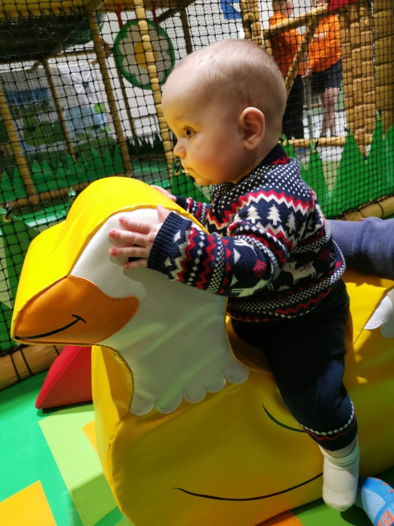 Baby sat on a large soft play duck in the baby area