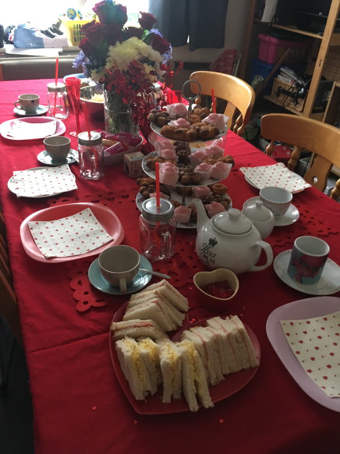 Dining table laid out with red table cloth and tea party for Valentine's Day