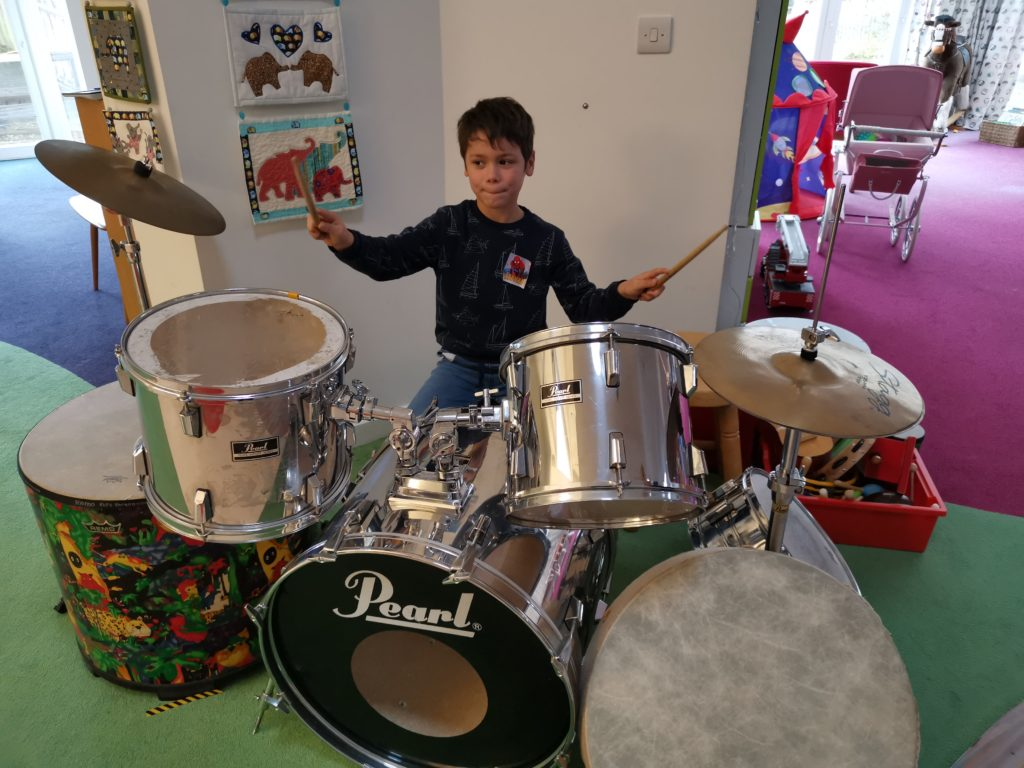 Cody playing a big drum kit at Helen and Douglas house