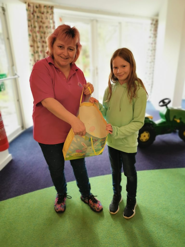 Lois giving craft supplies donation to Helen and Douglas house