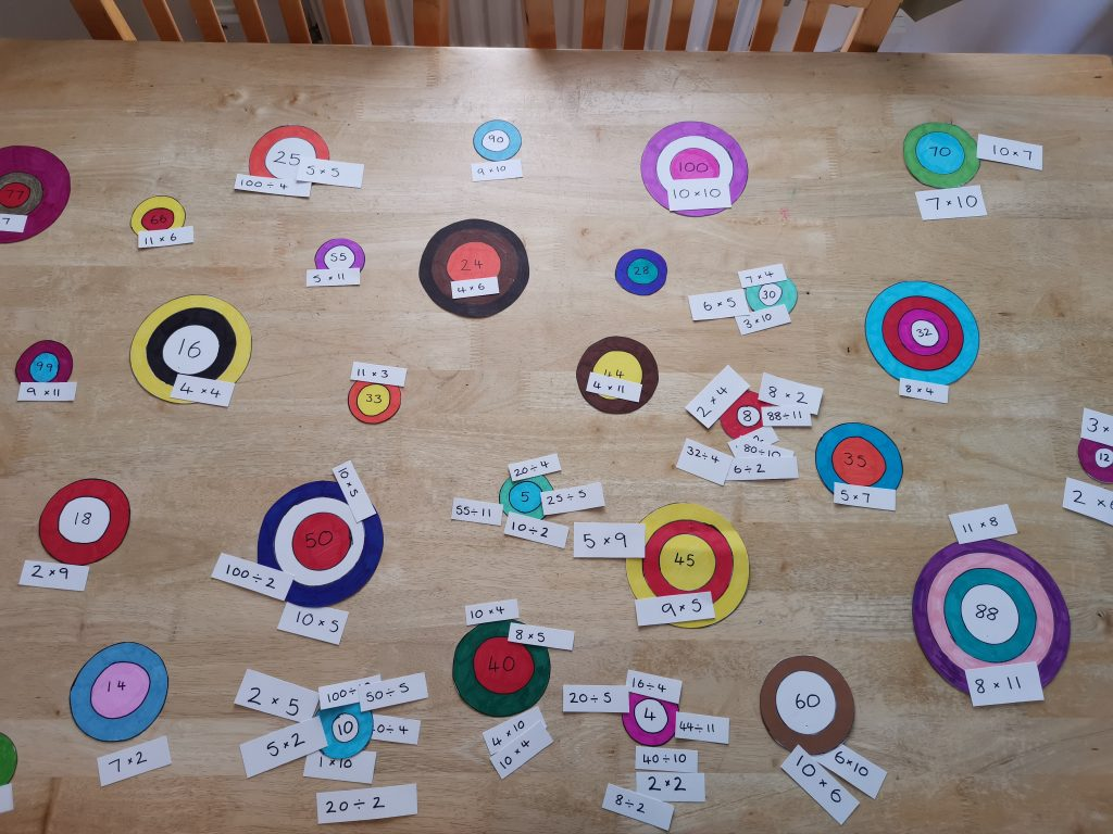 Number targets laid out on the table with time table question cards matched to the correct number target