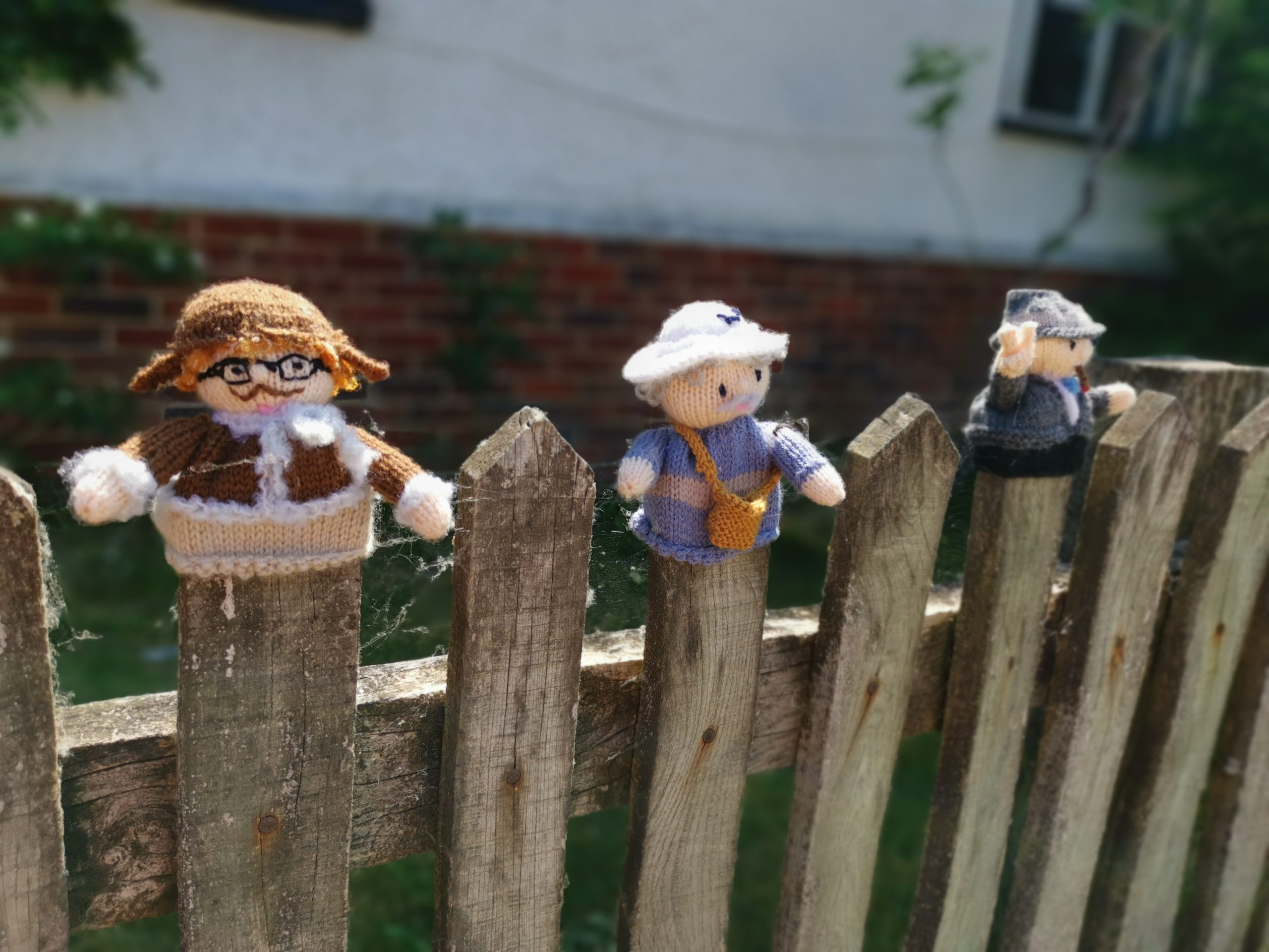 East Hendred village knitted characters sat on fence posts