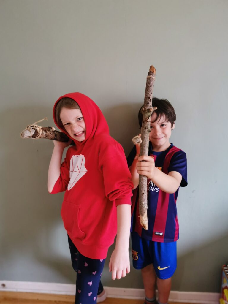Cody and Lois holding stone age hunting tools