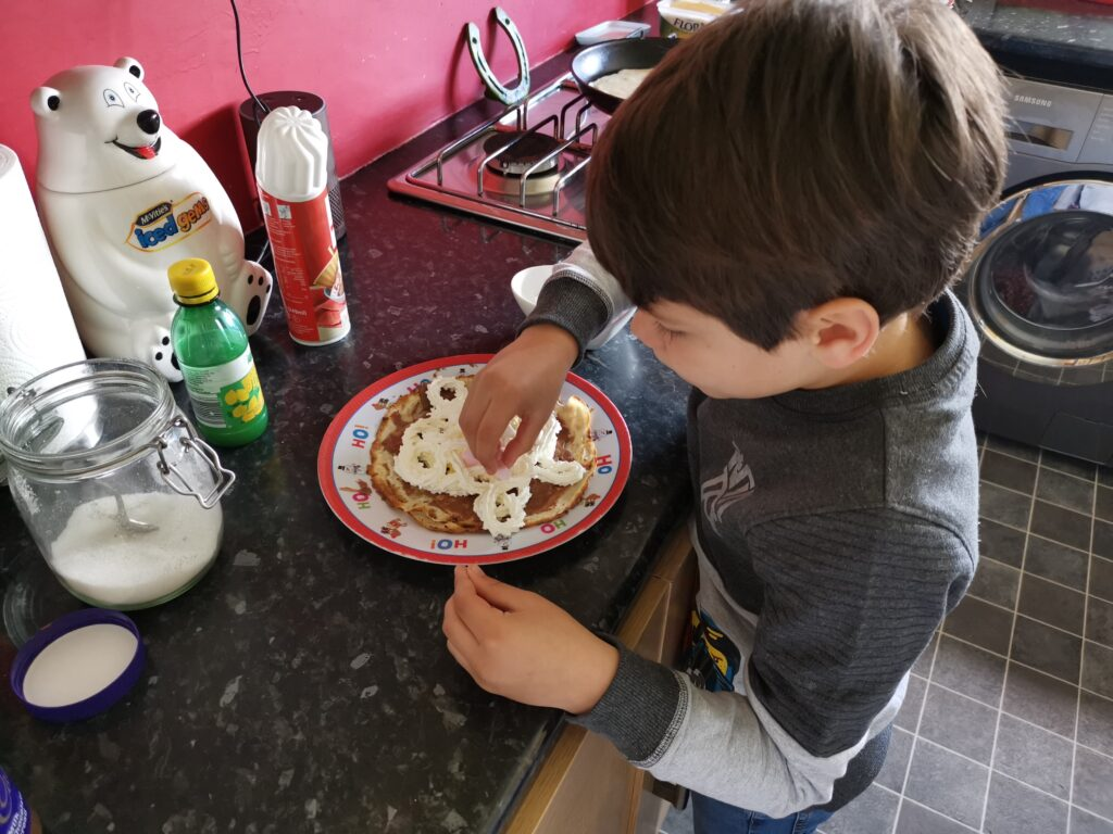 Cody putting toppings on pancakes