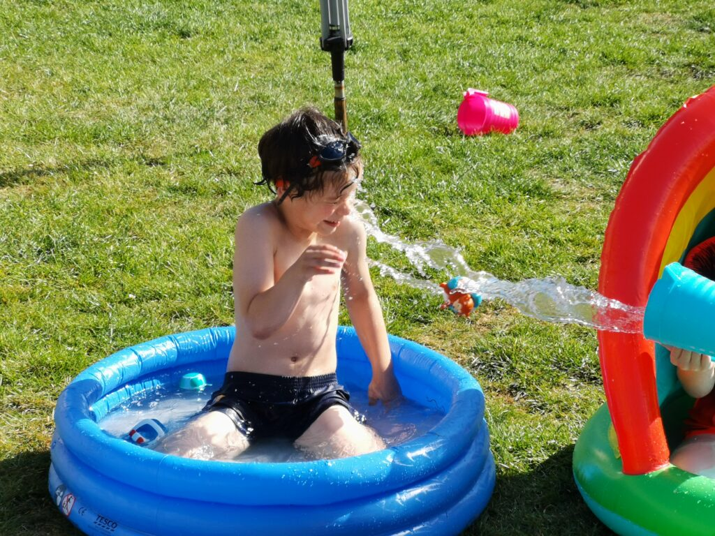 cody having a bucket of water thrown at him in paddling pool