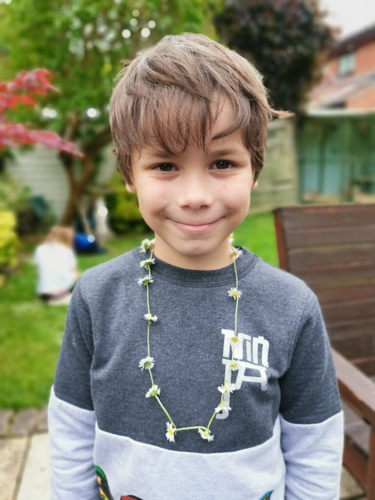 Cody wearing a daisy chain in the garden