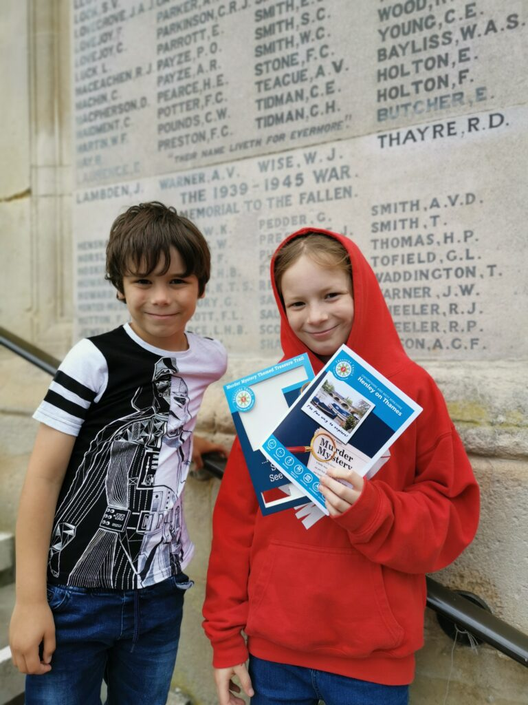 kids holding treasure trail booklet in front of town hall