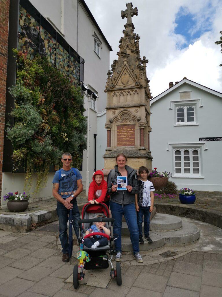 family group stood beside memorial