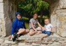 kids sat in window of castle ruin