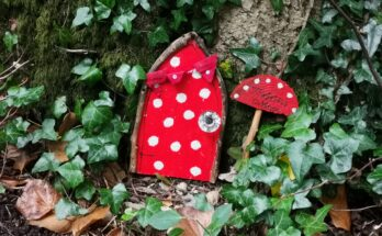 Red spotty fairy doors with toadstool sign next to it