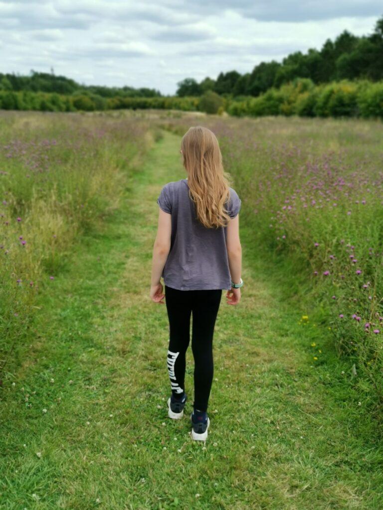 walking away along grass path in wildflower meadow
