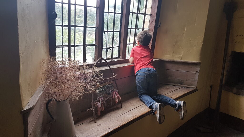boy looking out of farmhouse window