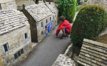 Boy looking in window of model building